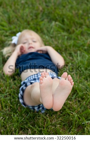 Little girl laying in grass holding bare feet up to camera - stock photo