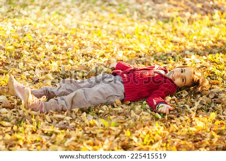 Little girl laying in leafs - stock photo