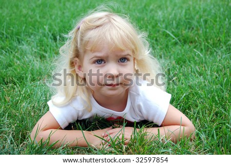 little girl laying in the grass - stock photo