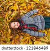 Little Girl Laying On A Heap Of Yellow Leaves - stock photo