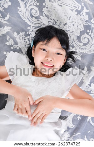 little girl laying on in bed with hands gesture - stock photo