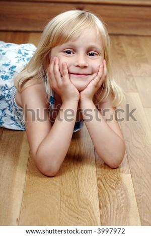 Little girl laying on the floor - stock photo