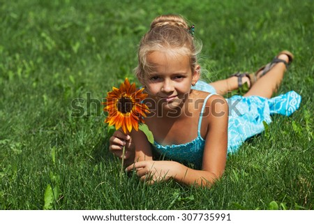 Little girl laying on the summer grass with a flower - copy space - stock photo