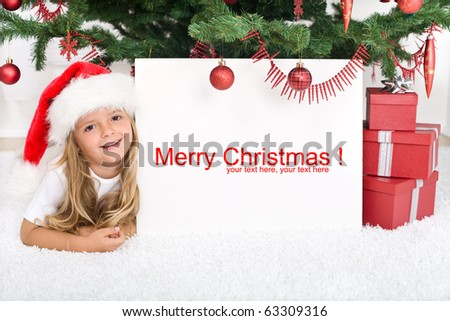 Little girl laying under the christmas tree with banner for text - stock photo