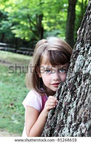 Little girl leaning against a large oak tree and looking at the viewer. Extreme shallow depth of field with selective focus on child. Some blur on tree. - stock photo