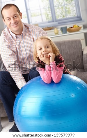 Little girl leaning on fit ball smiling, father watching from background. - stock photo