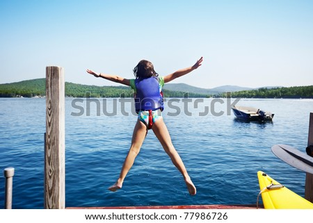 Little girl leaps off the end of the dock into a lake - stock photo