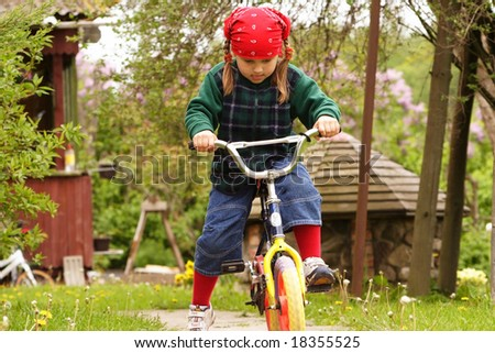 Little girl learning drive bicycle, very concentrated - stock photo