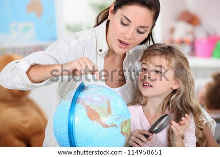 little girl learning geography with mom - stock photo