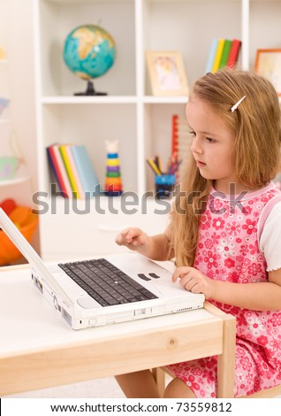 Little girl learning to handle a laptop computer in her room - stock photo