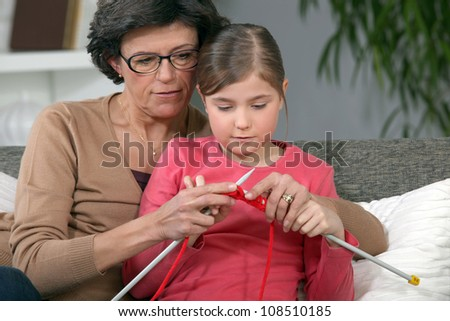 Little girl learning to knit - stock photo