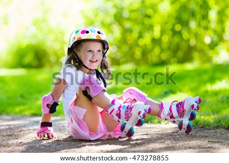 Little girl learning to roller skate in sunny summer park. Child wearing protection elbow and knee pads, wrist guards and safety helmet for safe roller skating ride. Active outdoor sport for kids.