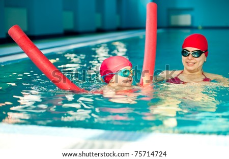 Little girl learning to swim with pool noodle - stock photo