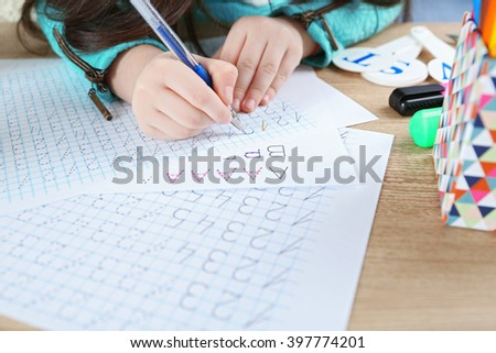 Little girl learning to write digits at the table