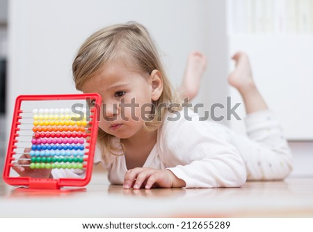Little girl learning with abacus lying on floor. - stock photo