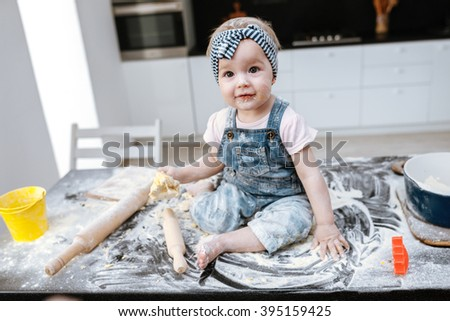 little girl learns to prepare dough in the kitchen - stock photo
