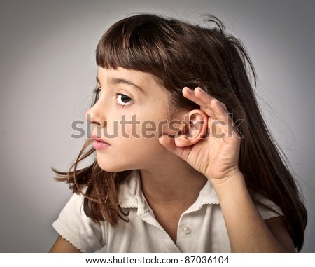 Little girl lending an ear to something - stock photo