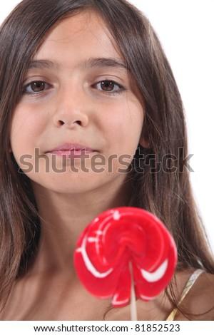 little girl licking a lollipop - stock photo