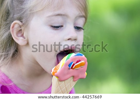 Little girl licking a sucker that is in the shape of an ice cream cone. - stock photo