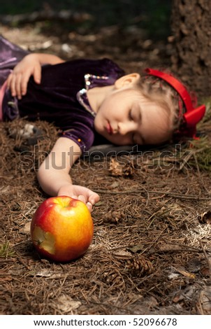 Little girl lie on a ground with apple - stock photo