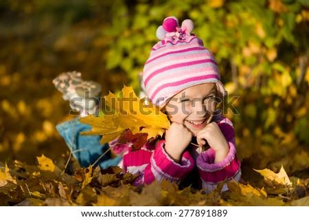 little girl lie on the autumn leaves - stock photo