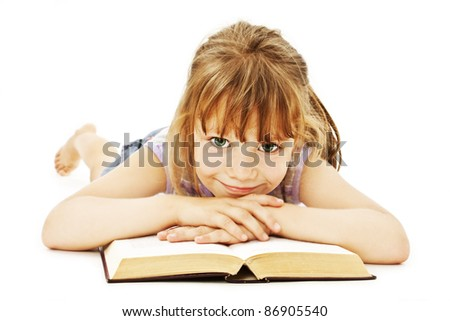 Little girl lieing on the floor and reading book - stock photo