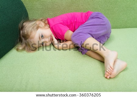 Little girl lies on a green couch. - stock photo