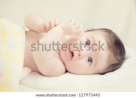 little girl lies on a yellow curtain - stock photo