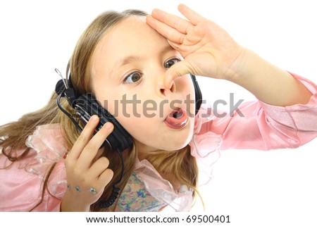 little girl listening to music and a real funny face - stock photo