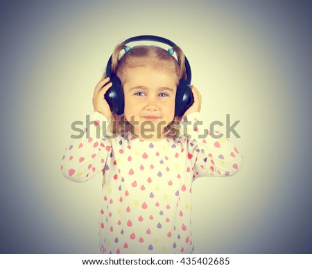 Little girl listening to music on headphones. - stock photo