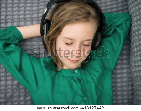 Little girl listening to the music in headphones. - stock photo