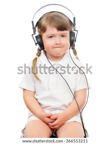 little girl listens music in ear-phones - stock photo