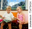 little girl listens to her big brother reading a childrens book at school - stock photo