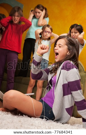 Little girl listens to music on headphones and  sings while friends cover their ears - stock photo