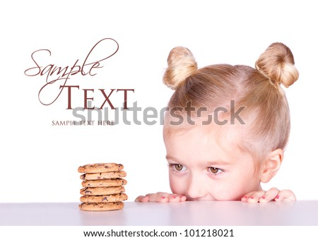 little girl looking at a pile of cookies on a counter or table isolated on white background