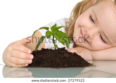 Little girl looking at a young plant wondering - closeup, isolated - stock photo