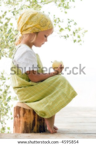 little girl looking at apple - stock photo