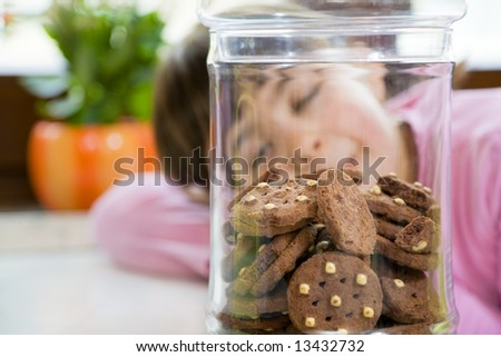 little girl looking at cookies in a jar - stock photo