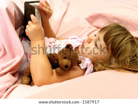 Little girl looking at her Bible before bedtime - stock photo