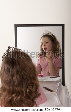 little girl looking at herself in mirror while playing make-up and fairy princess