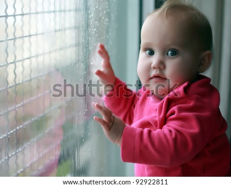 little girl looking at raindrops on the window - stock photo