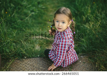 Little girl  looking at the camera. Nature outdoor setting,  - stock photo