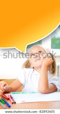 Little girl looking for a drawing concept wile painting picture on paper sheet. Indoors at classroom. Vertical Shot. Blank graphic balloon with copyspace for your text and logo. - stock photo