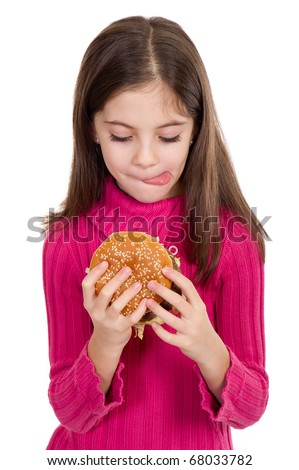 little girl looking  hamburger with tongue out - stock photo