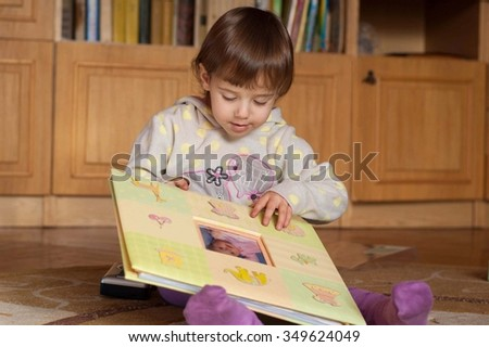 Little girl looking photo album in the room - stock photo