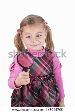 Little girl looking through a magnifying glass carefully. Isolated on white background - stock photo