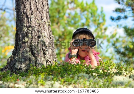 Little girl looking through binoculars with a surprised face - stock photo