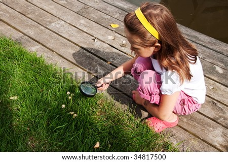 Little girl looking through magnifying glass on grass - stock photo