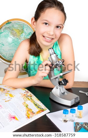 Little girl looking through microscope studying - stock photo