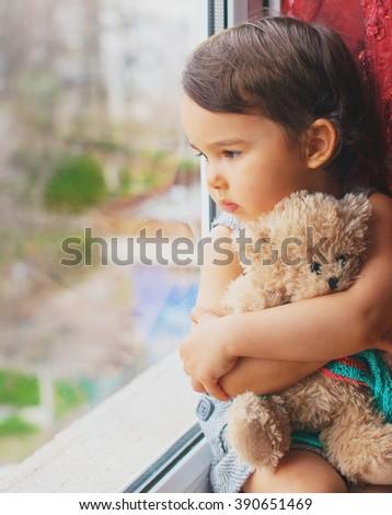 Little girl looking through window - stock photo